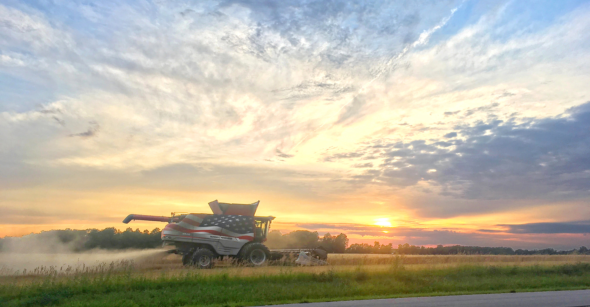 Combine in field, farming, sunset